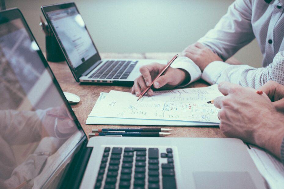 Mężczyźni przed laptopami analizujący dokument i symbolizuje to odpowiedź na pytanie jak podpisać dokument elektronicznie