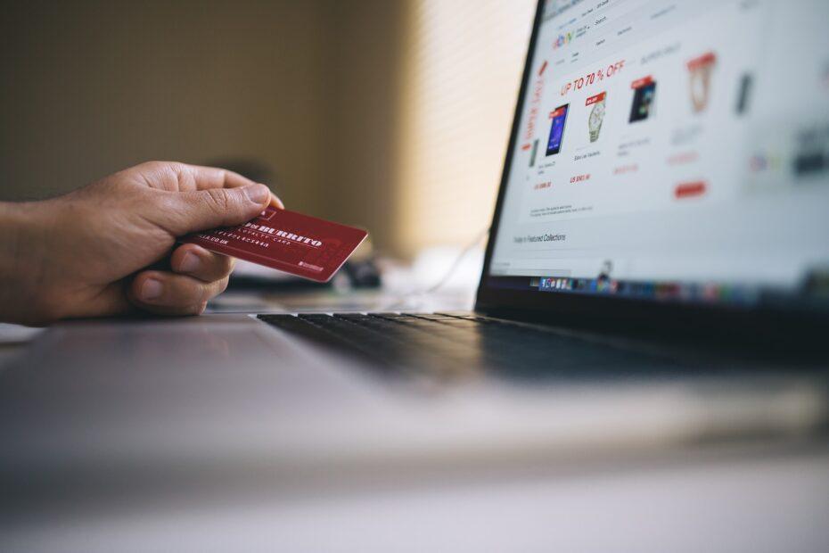 Ręką mężczyzny przed laptopem trzymająca kartę w ręku co symbolizuje jak zainstalować certyfikat na karcie kryptograficznej