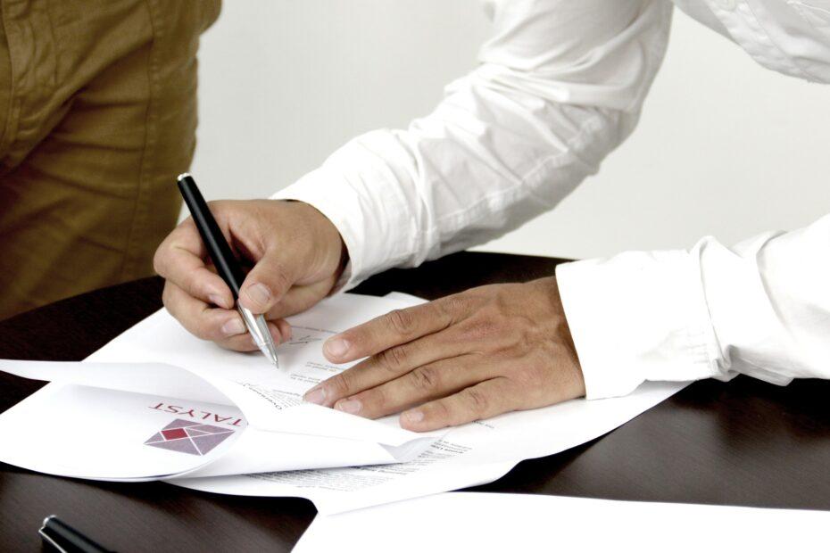 Mężczyźni podpisujący dokument i ma to symbolizować odpowiedź na pytanie jak uzyskać podpis elektroniczny